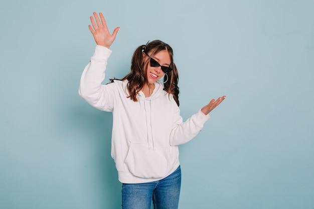 Indoor studio portret van charmante aantrekkelijke mensen met verzameld haar dragen witte trui dansen en plezier maken op geïsoleerde blauwe muur