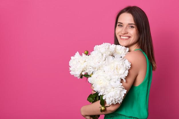 Indoor studio shot van charmante magnetische model bos van bloemen te houden