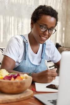 Indoor verticale shot van vrolijke zwarte afro-amerikaanse jonge meisje kijkt positief naar de monitor