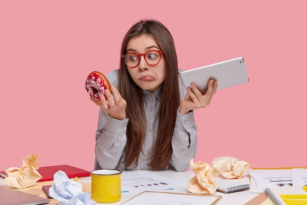 Indoor weergave van aarzelende vrouw houdt touchpad in de ene hand, smakelijke donut in andere, ziet er verwarrend uit, aarzelt wanneer junkfood eet, heeft pauze na papierwerk