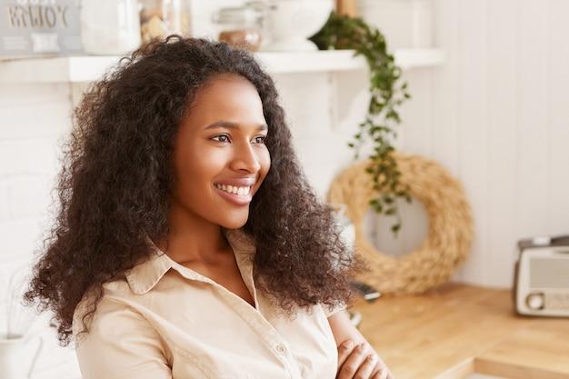 Indoor zijaanzicht van geweldige gelukkige jonge afro-amerikaanse vrouw met afro kapsel breed glimlachend, armen op haar borst houden, luisteren naar mooie muziek op de radio, taart bakken in gezellige keuken