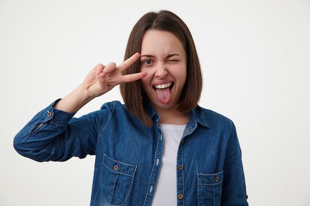 Indoos shot van vrolijke jonge brunette dame met natuurlijke make-up knipoog geven naar de camera en haar tong uitsteekt terwijl het verhogen van de hand met overwinning gebaar, geïsoleerd op witte achtergrond