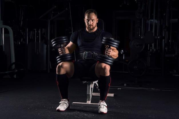 Indrukwekkende atleet zit op een bankje in de sportschool met twee halters op zijn benen