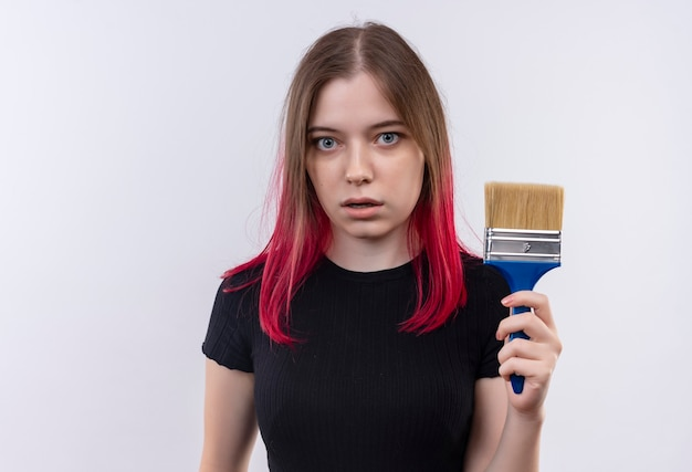 Indrukwekkende jonge mooie vrouw die de zwarte verfborstel van de t-shirtholding op geïsoleerde witte muur draagt