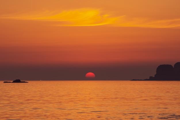 Indrukwekkende zonsondergang, grote halve zon die naar de horizon daalt, bij kust rond suwolbong-vulkaan, jeju, zuid-korea.