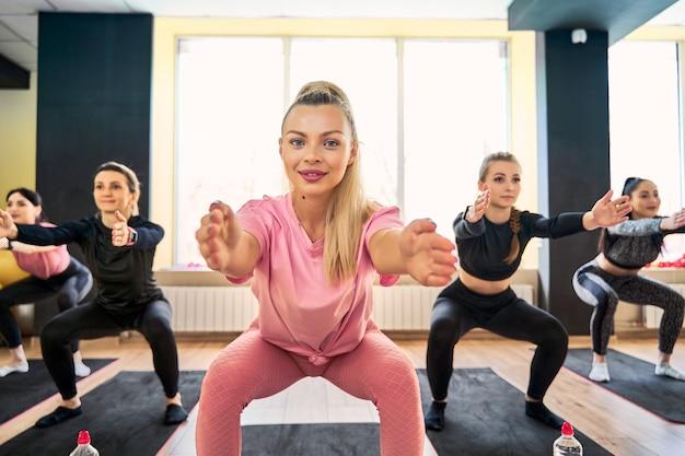 Indtructor vrouw doet squat oefening bij groepsfitness training