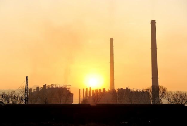Industrie, grote schoorsteen bij zonsondergang