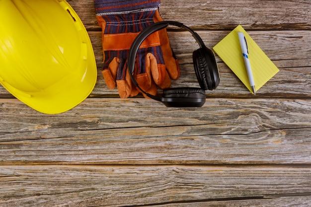 Industrie werknemer beschermende werkkleding veiligheidsnorm constructie veiligheid oorbeschermers leer in veiligheidshelm beschermende handschoenen notities papier op houten
