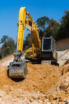 Industrieel graafwerktuig die aan bouwwerf werken om het land van zand en grond te ontruimen