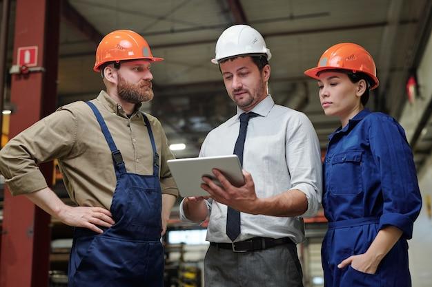Industrieel ingenieur in formalwear en veiligheidshelm machineonderdeel bespreken met werknemers met behulp van 3d-schets op tablet