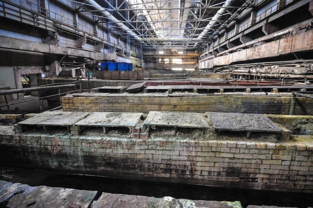 Industrieel interieur van oud fabrieksgebouw, oude roestige badkuip van zuur