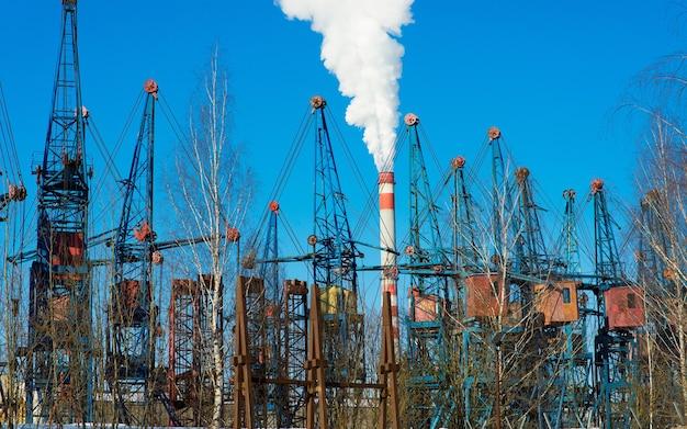 Industrieel landschap, kranen, pijpen met rook