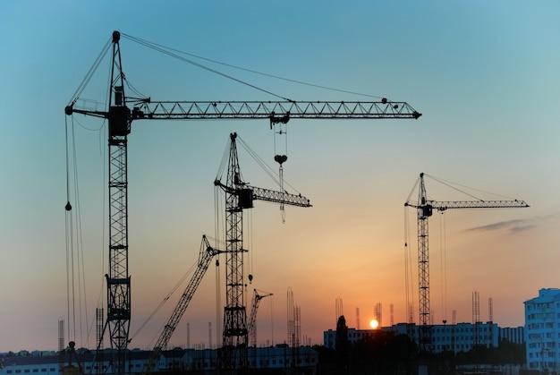 Industrieel landschap met silhouetten van kranen op de zonsondergang