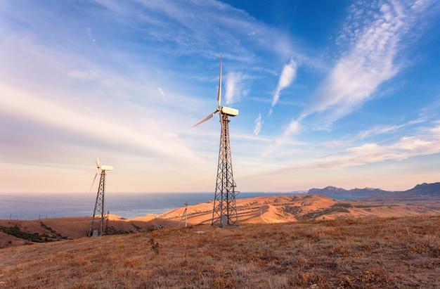 Industrieel landschap met windturbine die elektriciteit in bergen produceren bij zonsondergang