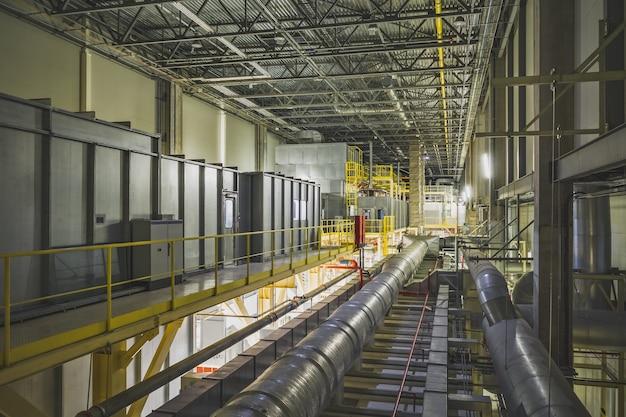 Industrieel luchtkoelsysteem en ventilatiepijpen onder het fabrieksplafond