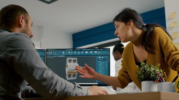 Industrieel ontwerper in gesprek met collega terwijl hij in cad-programma werkt aan het ontwerpen van een prototype van ...
