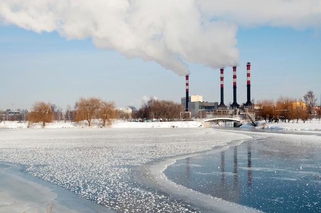 Industrieel stadsgezicht met bevroren rivier- en elektriciteitscentraleschoorstenen op achteruit in minsk, wit-rusland