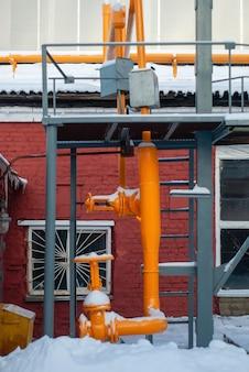 Industriële achtergrond - fragment van een fabrieksgasleiding met kleppen buiten in de winter