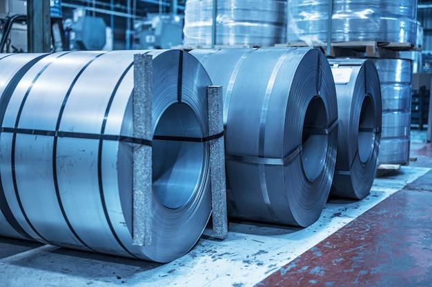 Industriële achtergrond. groot formaat stalen spoel opgeslagen in industrieel magazijn, blauw getinte afbeelding.