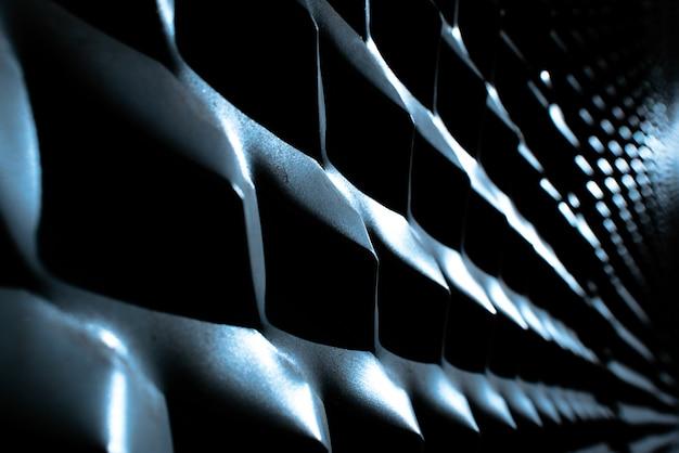 Industriële achtergrond met metaaltextuur die met sterke lichte en intense schaduwen en herhaald patroon wordt verlicht.