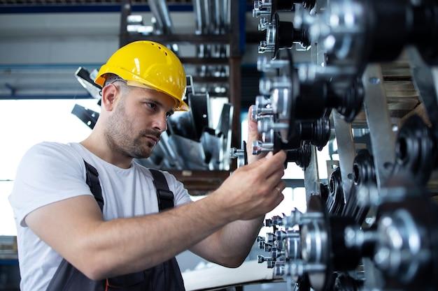 Industriële arbeider die bij productielijn in fabriek werkt