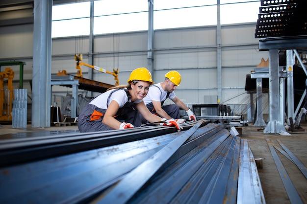 Industriële arbeiders die in fabriekshal met metaal werken