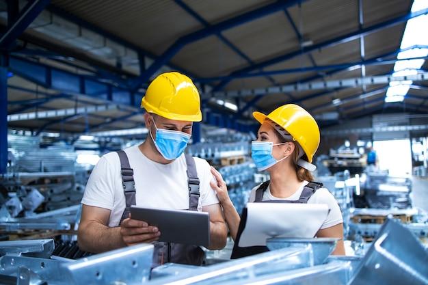 Industriële arbeiders met gezichtsmaskers beschermd tegen coronavirus analyseren resultaten van productie in fabriek