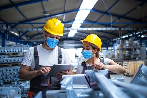 Industriële arbeiders met gezichtsmaskers beschermd tegen coronavirus discussiëren over productie in fabriek
