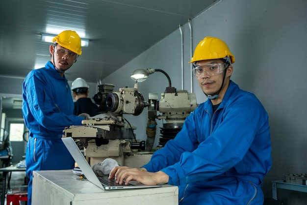 Industriële arbeiders met laptop die bij fabriek werken.