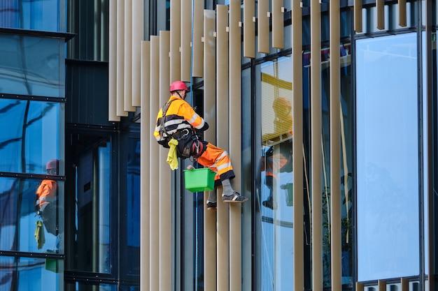 Industriële bergbeklimmen als een concept van een man wassen van ramen op een moderne wolkenkrabber
