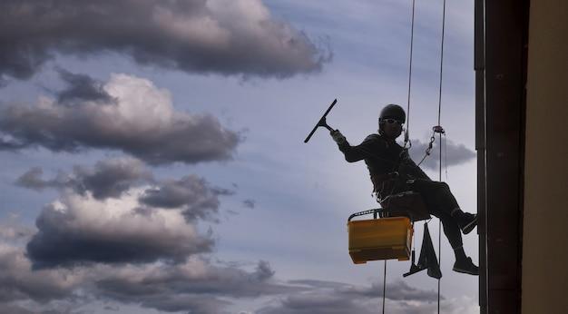 Industriële bergbeklimmer hangt over een woongevelgebouw terwijl hij de buitengevelbeglazing wast. rope access arbeider hangt aan de muur van het huis. concept van industriële stedelijke werken. ruimte kopiëren
