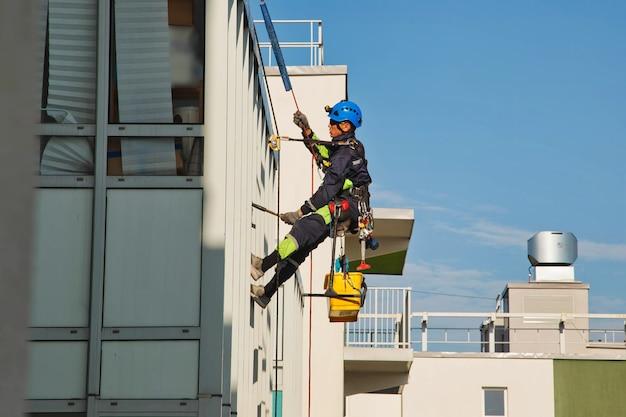 Industriële bergbeklimmer hangt over een woongevelgebouw terwijl hij de buitengevelbeglazing wast. rope access arbeider hangt aan de muur van het huis. concept van stedelijke werken. ruimte voor site kopiëren