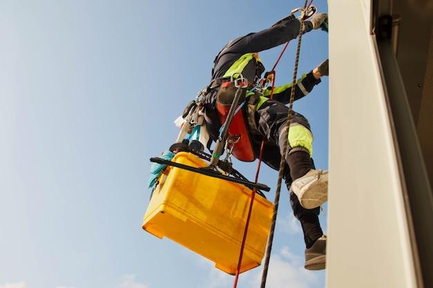 Industriële bergbeklimmer hangt over woongebouw tijdens het wassen van buitengevelbeglazing. rope access arbeider hangt aan de muur van het huis