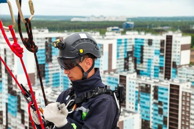 Industriële bergbeklimmer in uniform op woningbouw tijdens hoogbouwwerk. rope access arbeider op de muur van het huis. concept van industriële stedelijke werken. ruimte voor site kopiëren