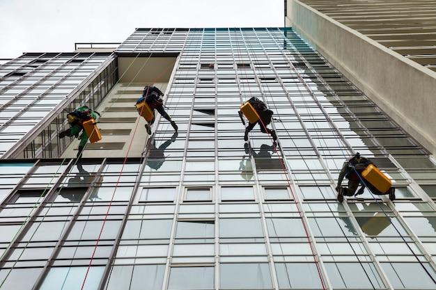 Industriële bergbeklimmers hangen over een woongevelgebouw terwijl ze de buitengevelbeglazing wassen. kabelwerkers hangen aan de muur van het huis. concept van industriële stedelijke werken. ruimte kopiëren