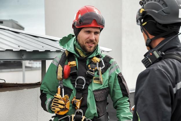 Industriële bergbeklimmers in uniform op dak woningbouw tijdens hoogbouwwerk. kabeltoegangsarbeiders op dak van huis. concept van industriële stedelijke werken. ruimte kopiëren