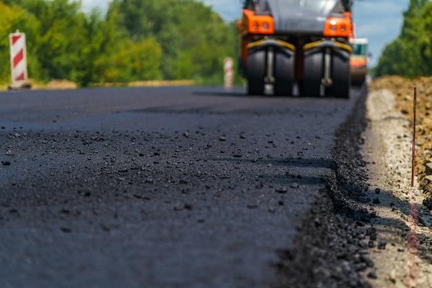 Industriële bestratingsvrachtwagen. het leggen van vers asfalt op de bouwplaats. zware machine-industrie. machinebouw.