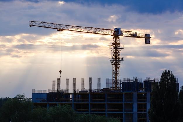 Industriële bouwkranen en de bouw van silhouetten over zonsopgang.