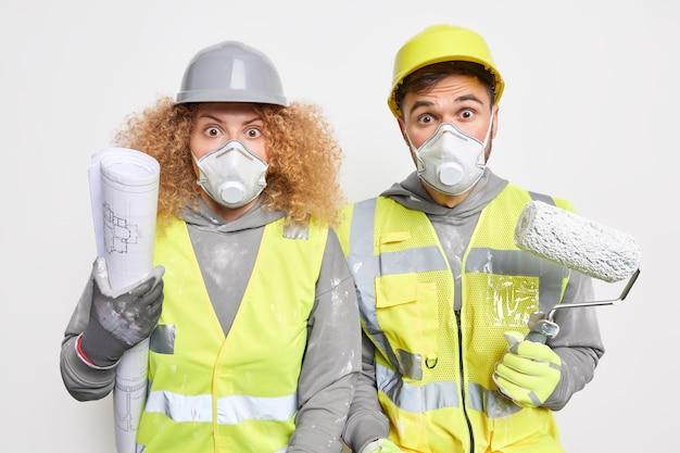 Industriële dienst. geschokte vrouwelijke en mannelijke werknemers in veiligheidsuniform beschermend gezichtsmasker houden bouwgereedschap en blauwdruk vast