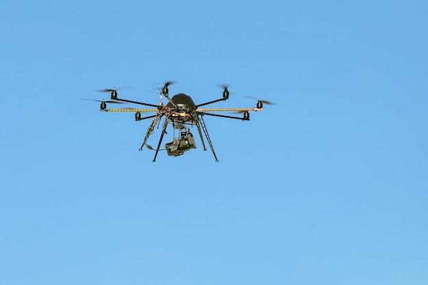 Industriële drone met een videocamera met blauwe lucht