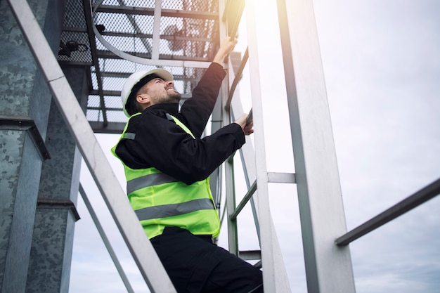 Industriële fabriek bouwvakker klimmen metalen ladder van productie-installatie in zonsondergang.