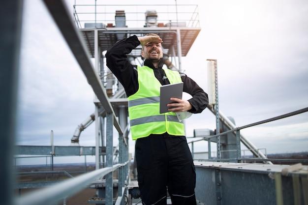 Industriële fabrieksarbeider staande op hoge metalen constructie van productie-installatie.