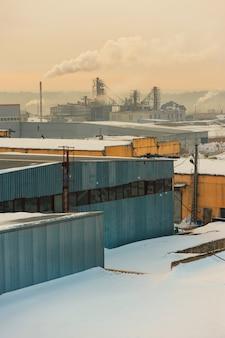 Industriële gebouwen in de mist op de blauwe hemel backgrond. magazijnen. rook uit de pijp. smog.