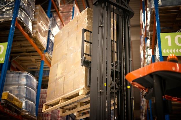 Industriële heftruck machine hijs palet vol kartonnen dozen en plaatst ze op planken in distributie magazijn faciliteit
