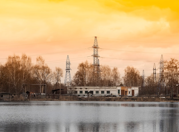 Industriële hoogspanningslijnen op de achtergrond van de zonsondergangrivier