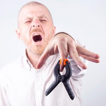 Industriële klem kneep in de vinger van een man