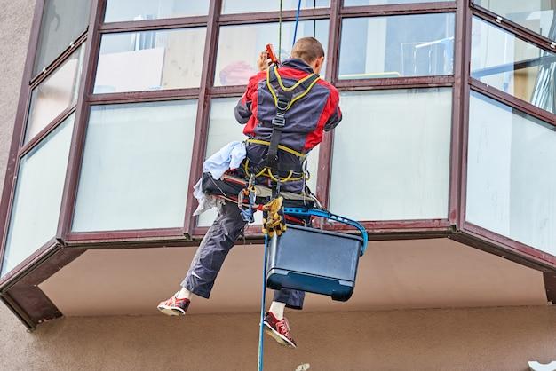 Industriële klimmer schoonmaak venster bij het bouwen in de stad