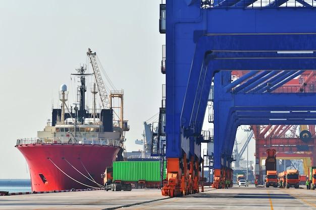 Industriële logistiek en transport van vrachtwagens in containerwerf voor logistiek en vrachtbedrijf in de scheepvaarthaven