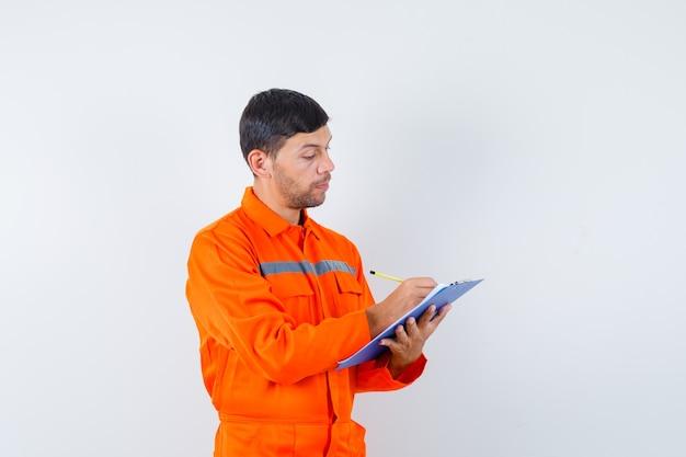 Industriële man die aantekeningen maakt op klembord in uniform en op zoek naar druk, vooraanzicht.