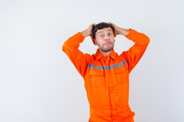 Industriële man die het hoofd vastgrijpt met de handen in uniform en er hulpeloos uitziet. vooraanzicht.